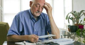 Senior man somberly looking at bills and paperwork © Burlingham/Shutterstock.com