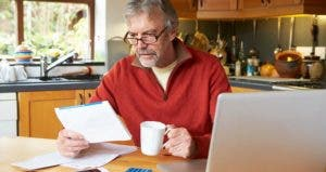 Mature man in red fleece pullover going over finances in kitchen | iStock.com/omgimages
