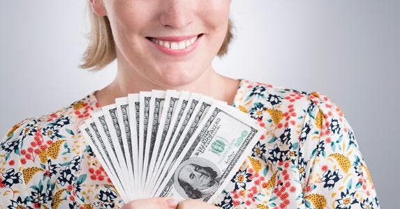 Smiling woman in floral shirt holding $100 bills