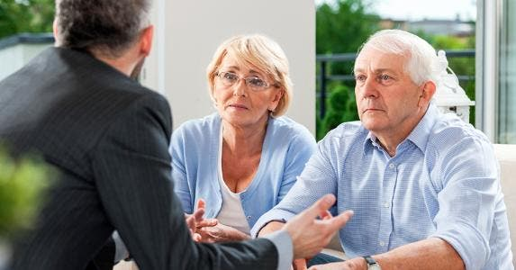 Senior couple talking seriously with adviser