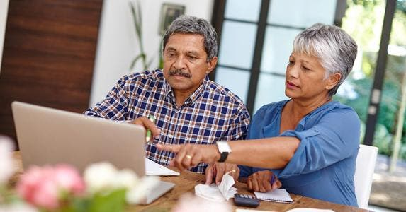 Seniors working on budget in the kitchen © iStock