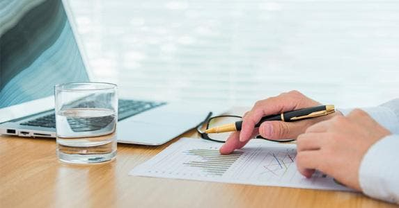 Financial adviser looking over line graphs © iStock