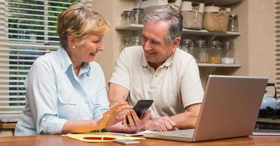 Senior couple laughing together while budgeting © iStock