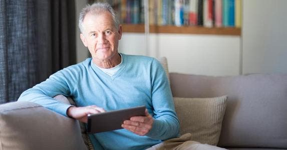 Senior male in light blue sweater browsing tablet | Alistair Berg/DigitalVision/Getty Images