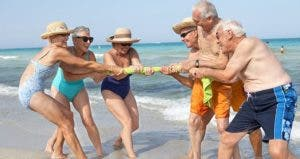 Seniors playing tug-o-war on the beach | Rolf Bruderer/Getty Images