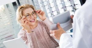 Mature woman trying on eyeglasses in optical shop | Iakov Filimonov/Shutterstock.com