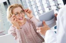 Mature woman trying on eyeglasses in optical shop | Iakov Filimonov/Shutterstock.com