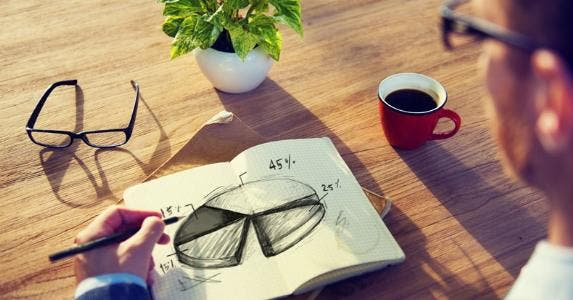 Man with a notebook drawing a pie chart © Rawpixel/Shutterstock.com