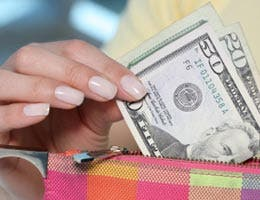 Woman pulling $50 bill from her wallet