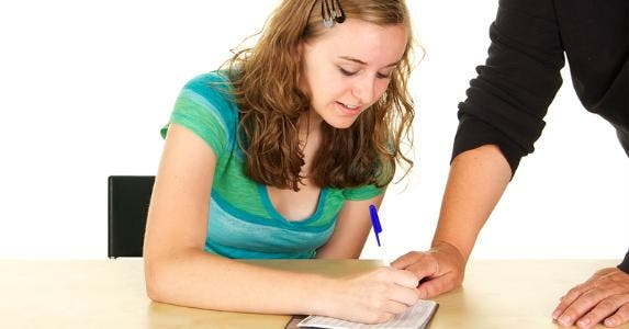 Teen writing in checkbook © iStock