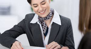 Teller going over new paperwork © racorn/Shutterstock.com