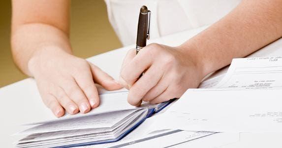 Woman writing in checkbook © AVAVA/Shutterstock.com
