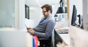 Male in grey cardigan browsing smartphone in the office | Hero Images/Getty Images