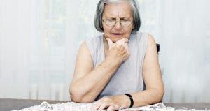 Worried senior woman sitting at desk with hand on chin © baki/Shutterstock.com