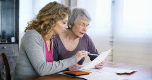 Senior woman sitting at table with younger woman looking at paperwork © Image Point Fr/Shutterstock.com