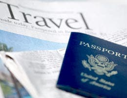 Travel section of newspaper and a passport