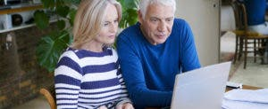 Senior couple sitting at a table looking at a laptop © Image Point Fr/Shutterstock.com