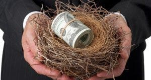 Man holding nest with large roll of money inside © iStock