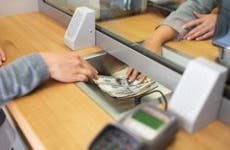 Teller passing cash to customer through bank window | Syda Productions/Shutterstock.com