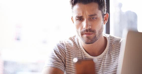 Man wearing striped shirt using smartphone © iStock