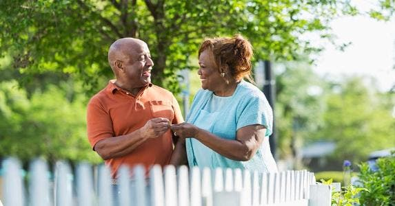 Happy couple standing outside by their picket fence | iStock.com/Susan Chiang