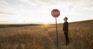 Man looking up at a stop sign | HeroImages/Getty Images