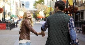 Young couple holding hands walking in city | HeroImages/Getty Images