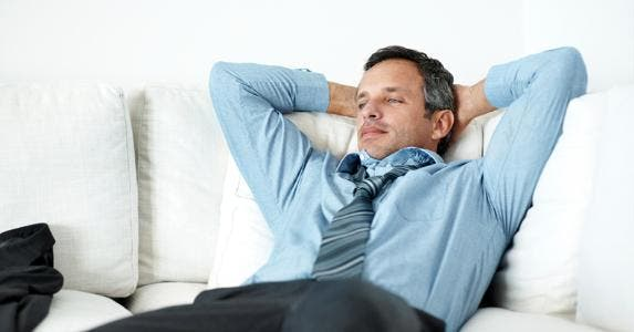Man in suit lounging on the couch © iStock