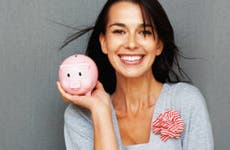 Smiling young woman holding piggy bank © Yuri Arcurs - Fotolia.com