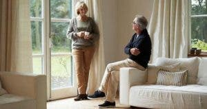 Senior couple talking in beige living room | Morsa Images/Getty Images