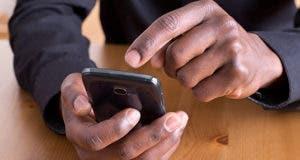 Man using smartphone at desk © photka/Shutterstock.com
