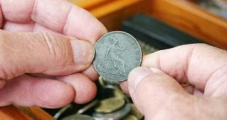Man holding old 1901 British penny © Sue McDonald/Shutterstock.com