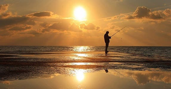 Man fishing on the beach at sunset
