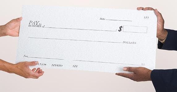 Two people holding a large blank check | Image Source/Getty Images