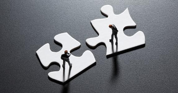 Businesesmen figurines standing on puzzle pieces © iStock