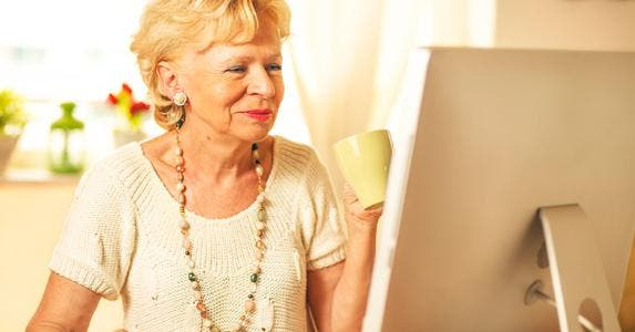 Senior woman holding cup of drink while on the computer © iStock