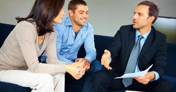 A couple sitting with their financial adviser © iStock