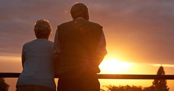 Senior couple looking over horizon sunset | iStock.com/PeopleImages