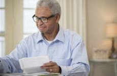 Older man happily doing paperwork | Terry Vine/Blend Images/Getty Images