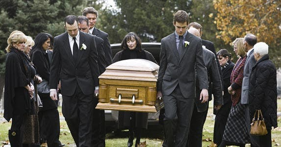 Men at funeral carrying casket to burial plot