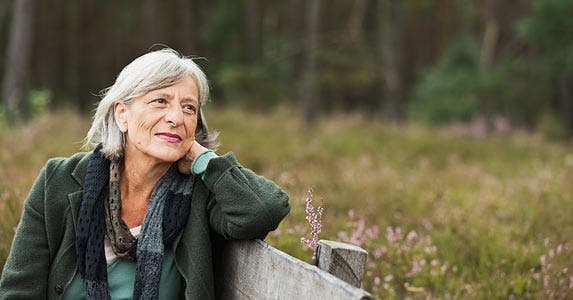 Senior woman sitting on a park bench, looking right