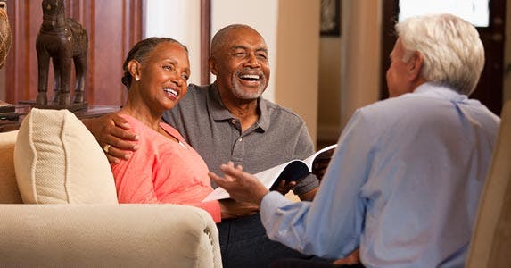 Senior couple meeting with financial adviser, laughing together
