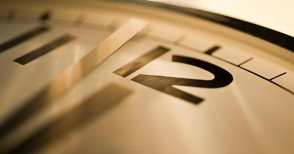 Close up of analog clock on 12 o'clock | Tetra Images/Getty Images