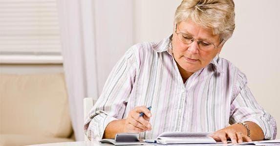 Mature woman balancing checkbook © AVAVA/Shutterstock.com
