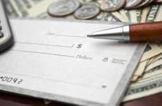 Calculator with white checks, wood pen and money | iStock.com/bezov