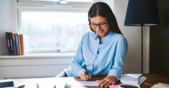 Woman writing a check in office | Uber Images/Shutterstock.com