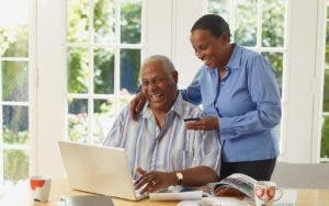 Couple looking at laptop and holding credit card