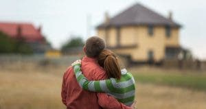 Couple hugging each other, lookinga at house in distance © luxorphoto/Shutterstock.com