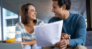 Couple smiling over paperwork © iStock