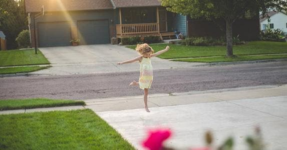 Young girl playing in driveway | Annie Otzen/Getty Images